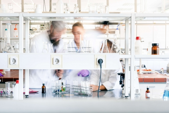 A blurred action photo of people working in a scientific lab