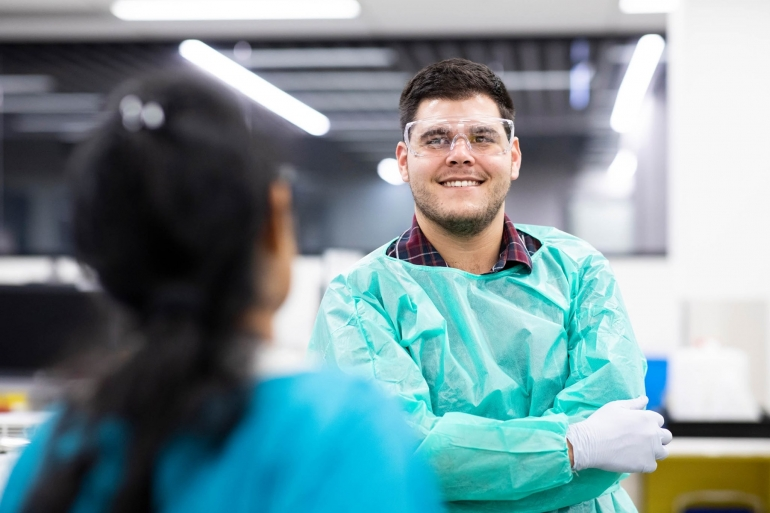 A student in lab wear smiling