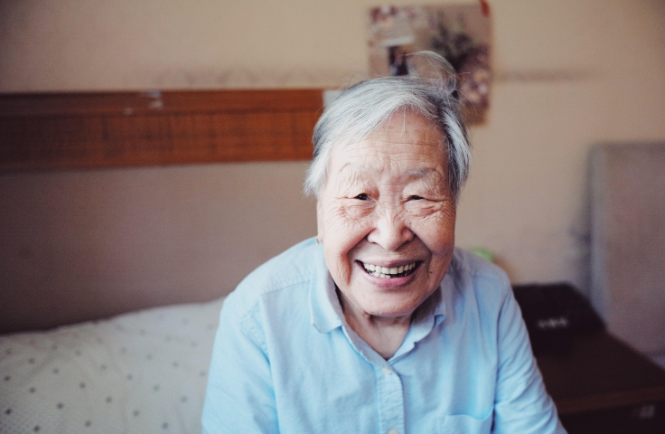 Elderly woman smiling and sitting on bed
