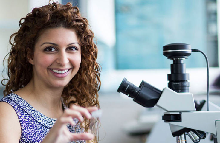 Woman with curly hair smiling in front of microscope