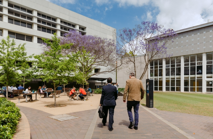 Two people walking through the business school