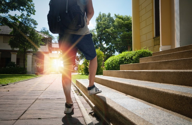 Student wearing blue shorts and backpack walking up stairs