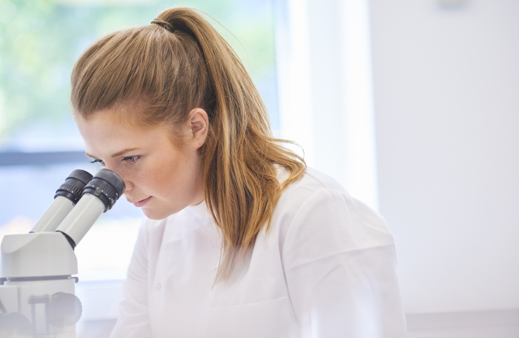 a female research scientist is analysing a sample on her microscope in a microbiology lab . the lab is brightly lit with natural light .