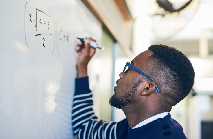 Man completing mathematics problem on white board