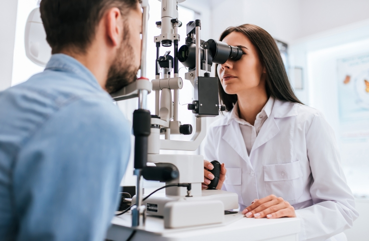 Optometrist observing another person's eyes