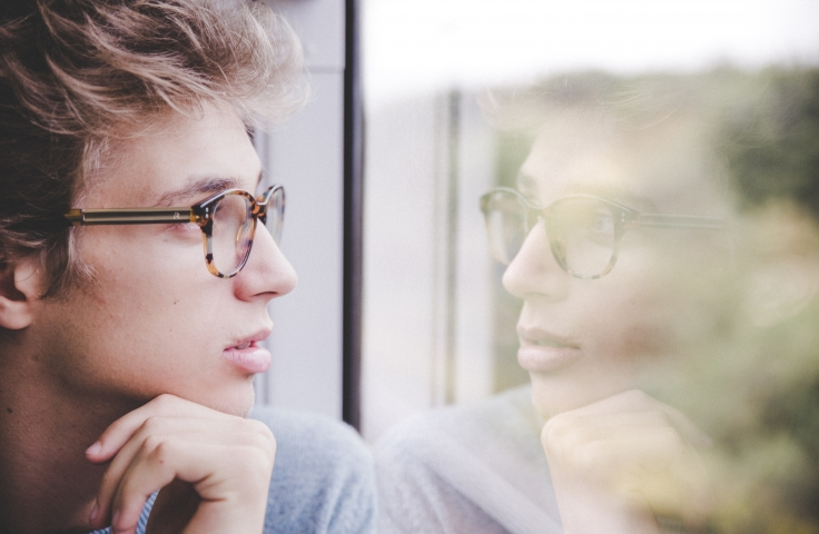A young man with glasses looking pensively out a window