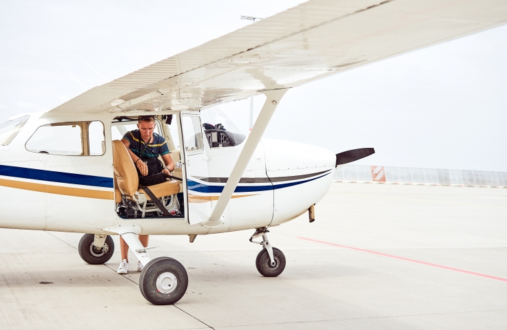 A young man sitting in the pilots seat of a grounded light plane